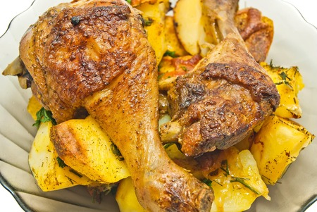 chicken leg: plate with chicken and potatoes on white background Stock Photo