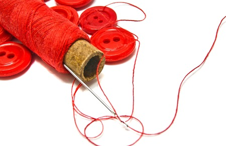 spool of red thread and buttons closeup on white