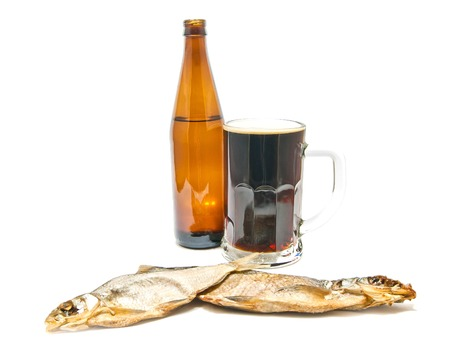 two salted fishes and dark beer on white background closeup photo