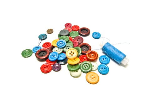 different buttons and spool of thread on white background