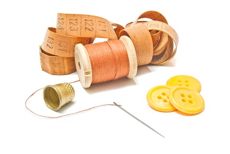 spool of thread, meter and yellow buttons on white Stock Photo