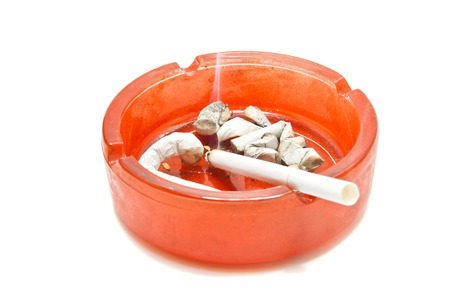 butts and cigarette in red ashtray on white closeup photo