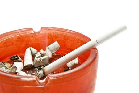 cigarette in glass ashtray on white background photo