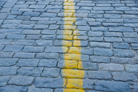 old stone pavement with yellow road markings