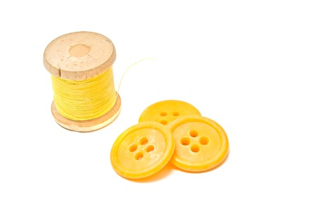 spool of yellow thread and plastic buttons closeup on white