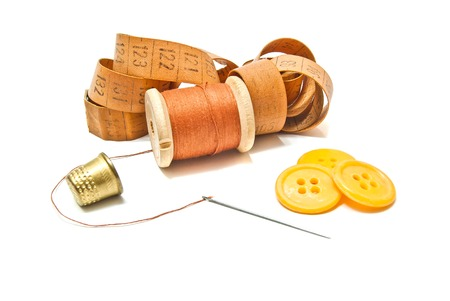 spool of thread, thimble and buttons on white background Stock Photo