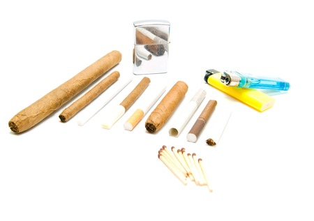 encendedores: varios cigarrillos, fósforos y encendedores detalle en blanco Foto de archivo