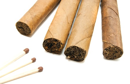 cigars: four cigars and matches on white background