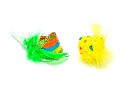 past midnight: pair of festive whistles with feathers on white closeup Stock Photo