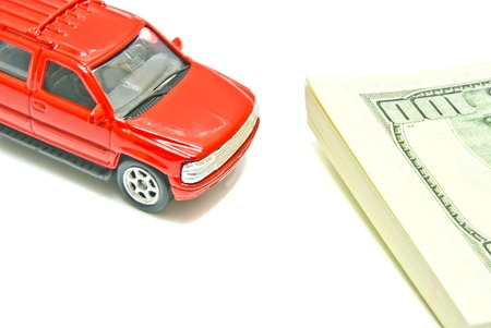 auto leasing: red car and dollar notes on white closeup