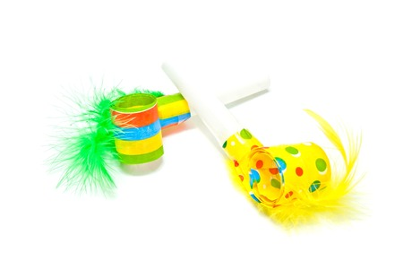 pair of festive whistles with feathers on white photo