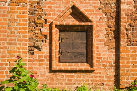 grates: closed window on a wall of old brick manor Stock Photo