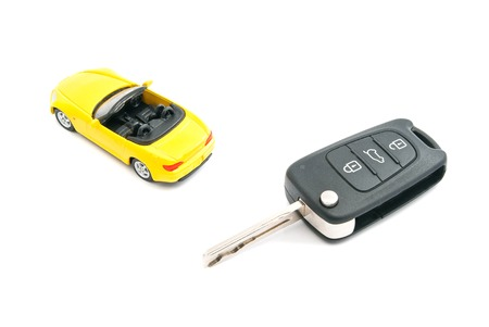 afford: keys and yellow sport car closeup on white