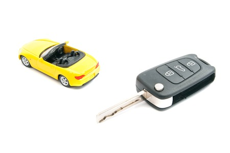 auto leasing: keys and yellow sport car on white closeup