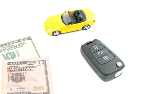 yellow car with keys and money on white background Stock Photo