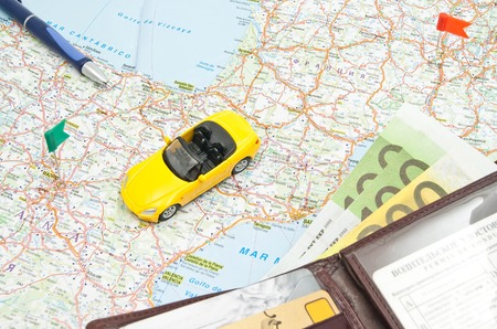 wallet, pen and yellow car on the map of Europe