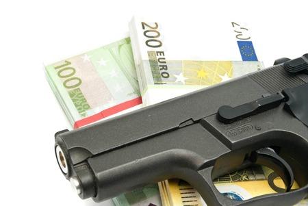 gunshot: gun and banknotes on white background closeup