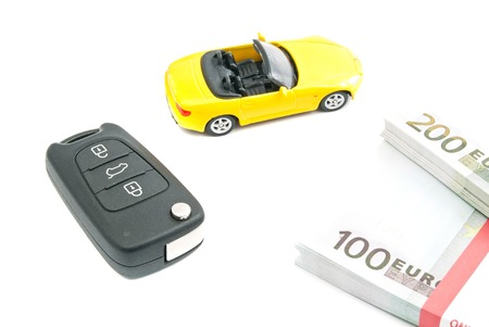 afford: yellow car with keys and money closeup on white Stock Photo