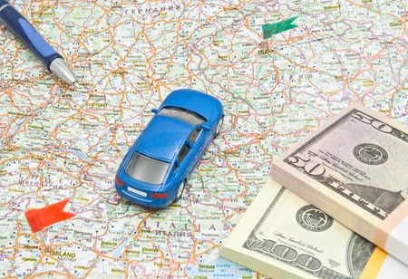 blue car on map of Europe with money and pen