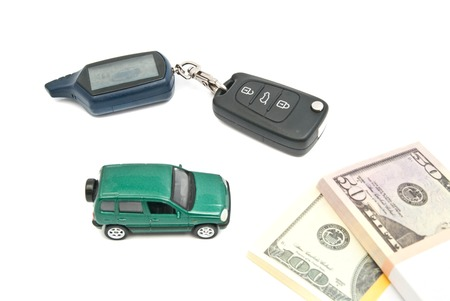 green car, keys and banknotes closeup on white background