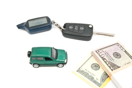afford: green car, keys and banknotes on white background closeup