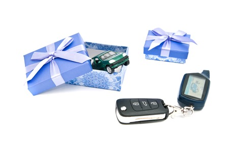 car keys, green car and blue gift boxes on white