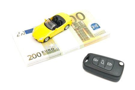 car keys, yellow car and banknotes on white background