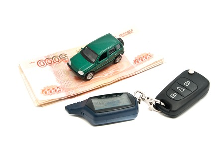 Russian banknotes, keys and green car on white closeup