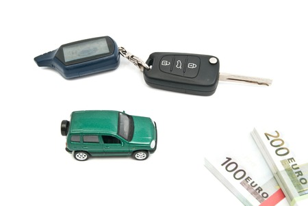 afford: green car, keys and banknotes closeup on white