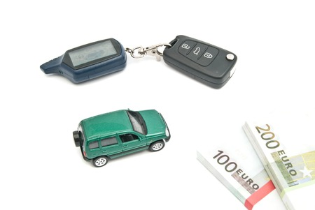 green car, keys and banknotes on white photo