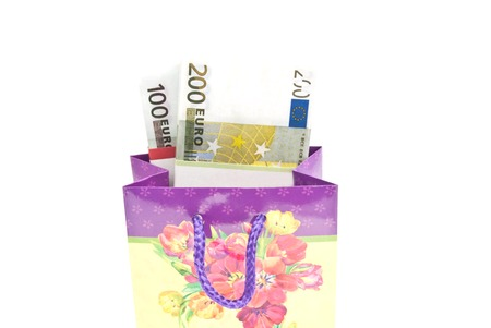 closed ribbon: Colorful gift bag with money on white background closeup