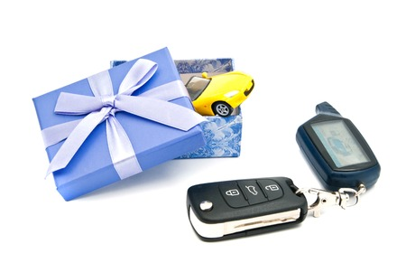 blue gift box: car keys, yellow car and blue gift box on white background
