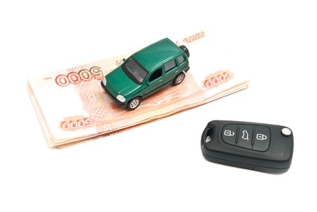 Russian banknotes, keys and green car on white