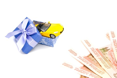 afford: yellow car in blue gift box and banknotes on white Stock Photo