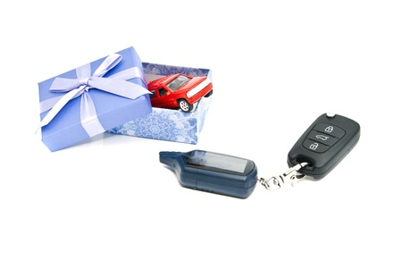 car keys, red car and blue gift box on white