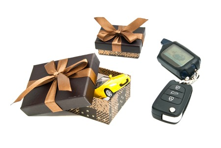 auto leasing: car keys, yellow car and brown gift boxes on white background Stock Photo