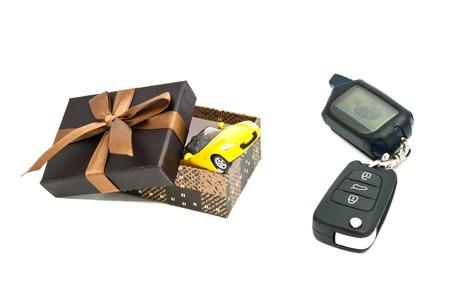 car keys, yellow car and brown gift box on white closeup