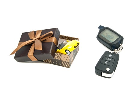 afford: yellow car, keys and brown gift box on white