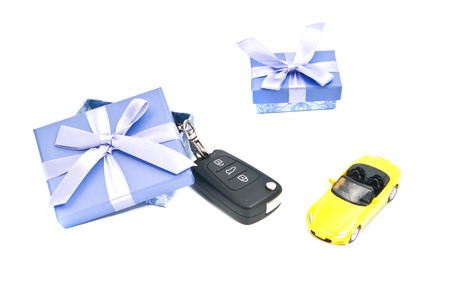 two gift boxes, car and keys on white closeup