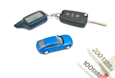auto leasing: blue car, keys and banknotes on white closeup