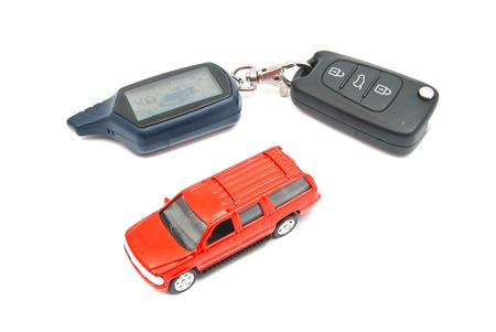 afford: red car and keys on white background closeup