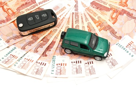 afford: green car, keys and banknotes closeup on white background
