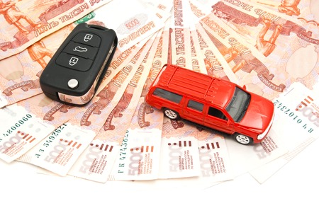 red car, keys and banknotes on white closeup photo
