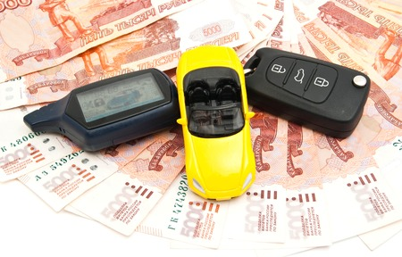 yellow car: yellow car, keys and banknotes on white
