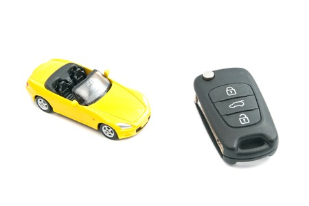 afford: yellow car and black car keys on white Stock Photo