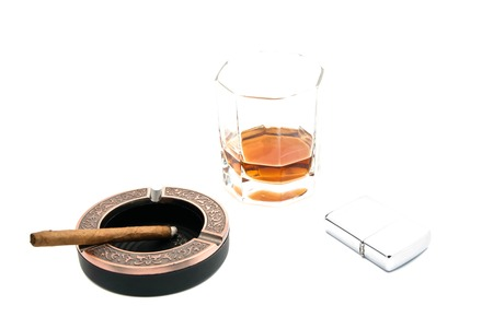 lighter, cigarillo in ashtray and whiskey on white