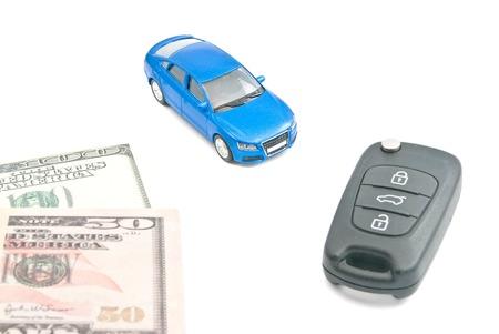 sell car: blue car, black car keys and dollar notes on white