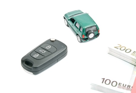 afford: Green car, black car keys and euro notes on white