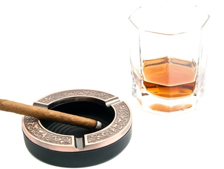 cigarillo in ashtray and alcohol on white background