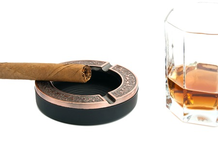 cigar in metal ashtray and whiskey on white closeup